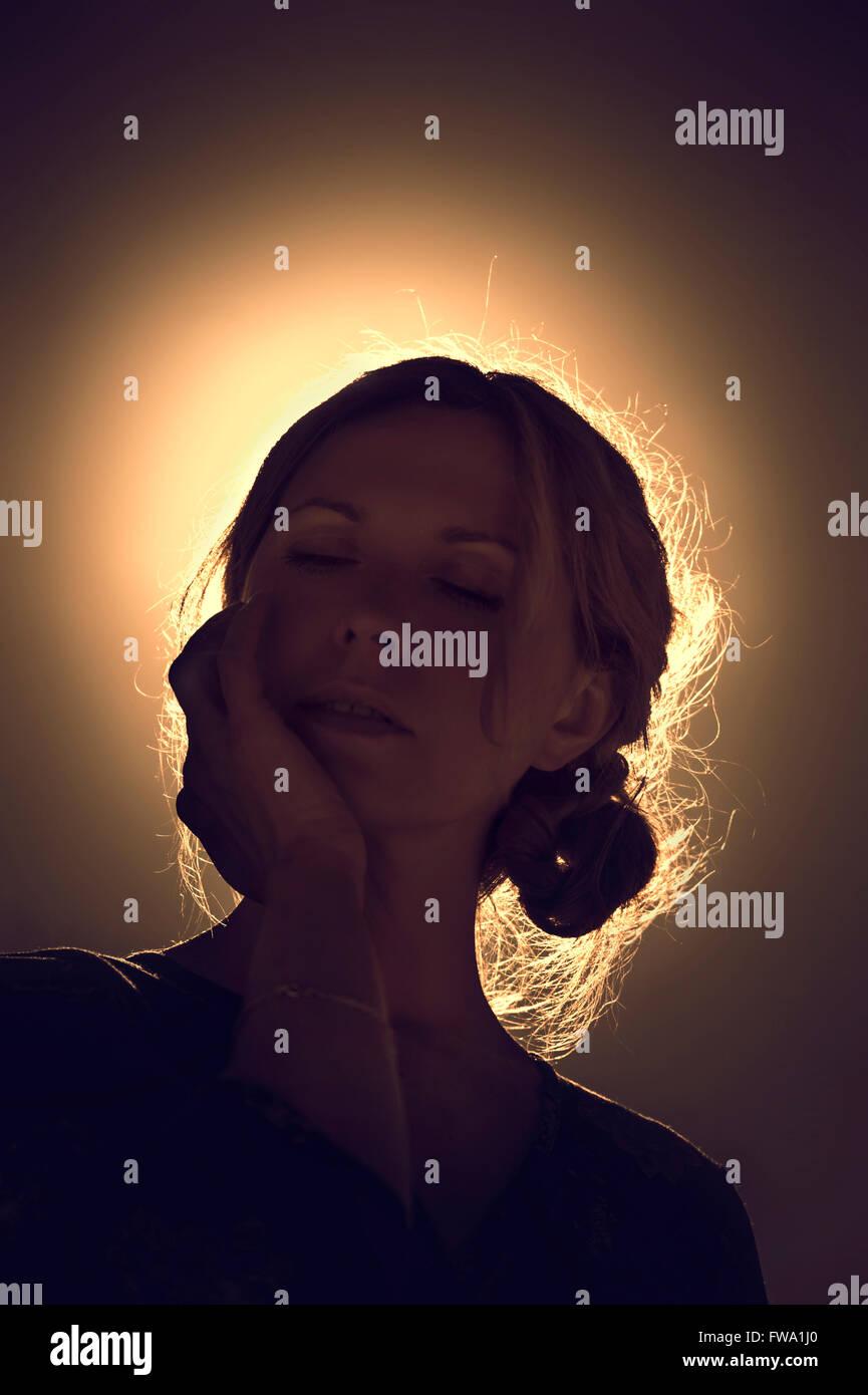 Portrait de jeune femme contre la lumière du soleil Photo Stock
