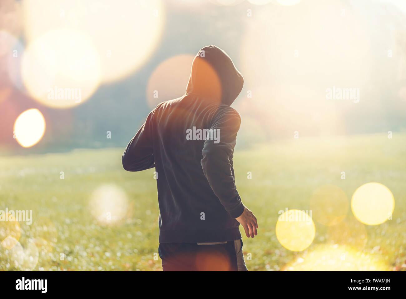 Méconnaissable hooded man jogging à l'extérieur, style de vie sain dans le parc au début de l'automne matin, tons rétro droit Banque D'Images