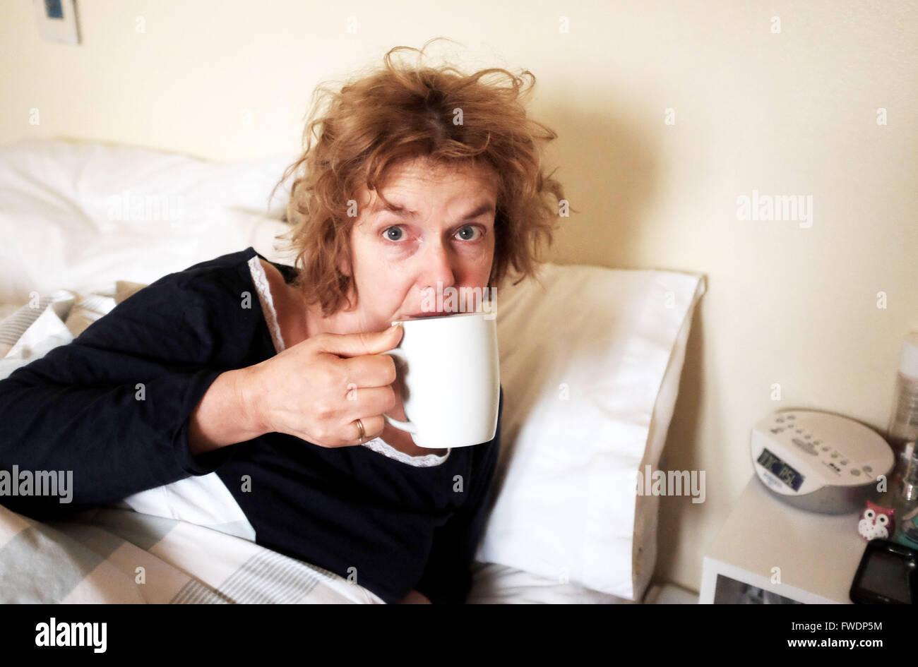Femme Au Reveil femme à la tasse de thé potable échevelée après le réveil le matin