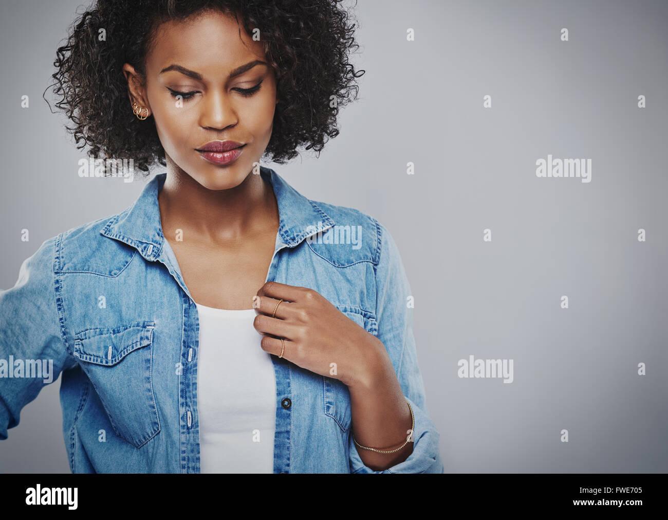 Thoughtful young African American Woman wearing une veste en jean décontracté debout avec les yeux baissés Photo Stock