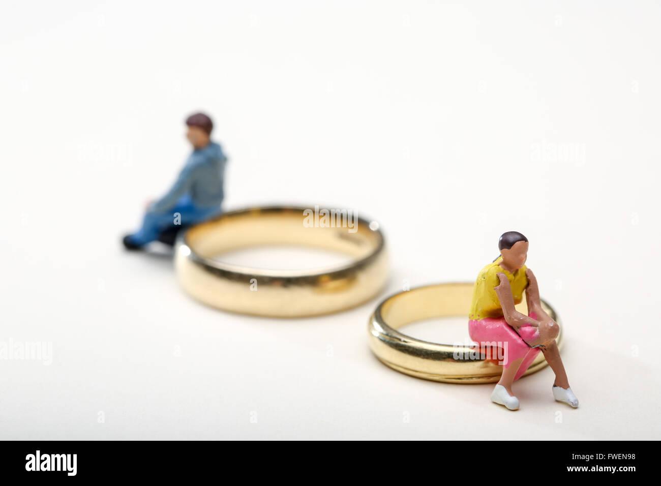 Concept de droit d'un couple assis sur les anneaux de mariage pour illustrer le divorce et la séparation Photo Stock
