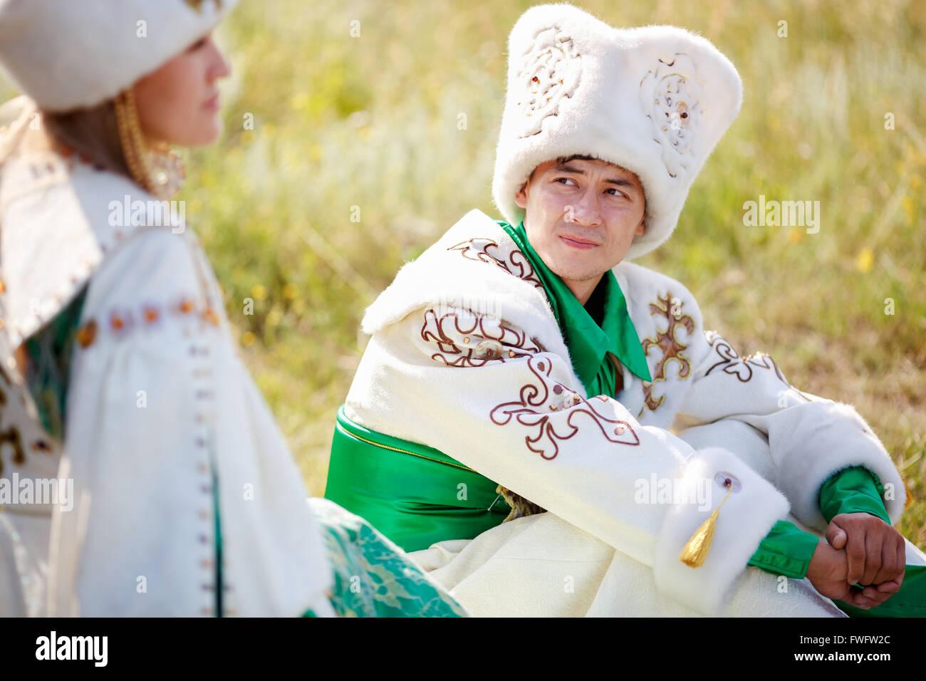 L'homme sur l'herbe en vêtements traditionnels regarde sa femme bien-aimée Photo Stock