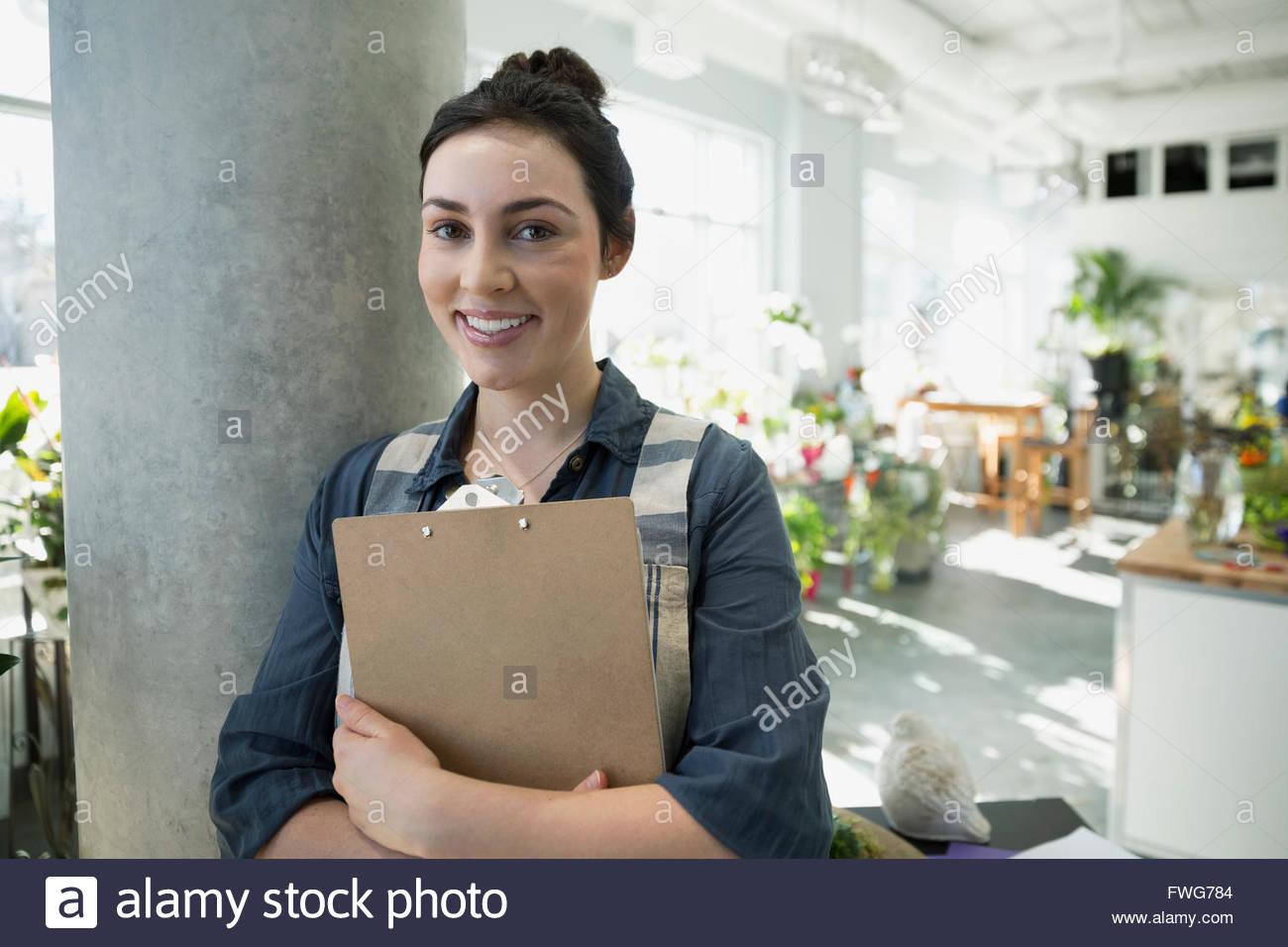 Portrait smiling florist avec presse-papiers dans le magasin de fleurs Photo Stock