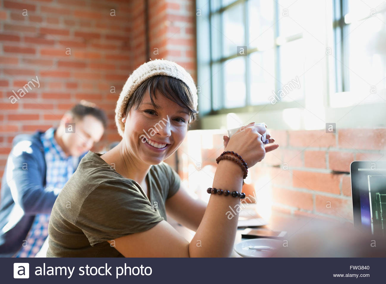 Portrait of smiling woman drinking coffee in coffee shop Photo Stock