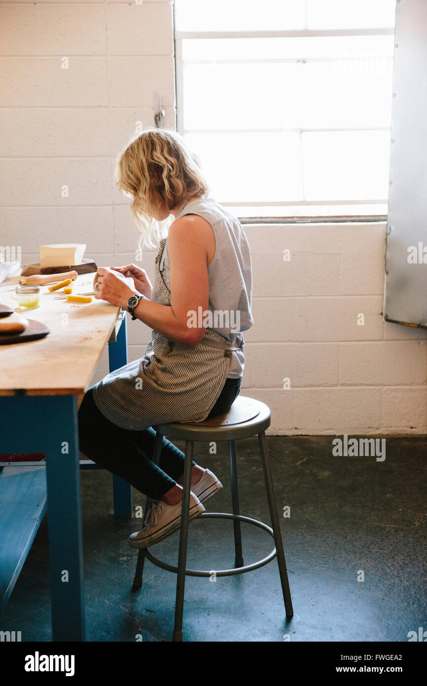Une femme assise sur un tabouret dans un atelier. Photo Stock