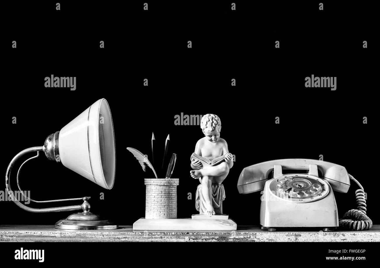 Lampes et ancien téléphone sur un sol en bois avec fond noir Photo Stock