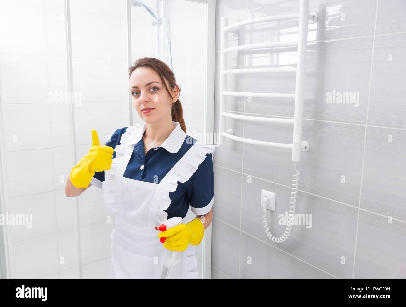 Certains jeunes employée de maison standing in robe bleue et tablier blanc avec Thumbs up geste tout en maintenant à côté de cabine de douche dans la salle de bains. Banque D'Images