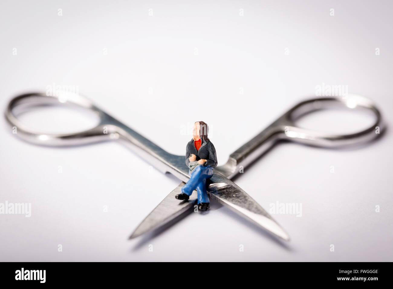 Image d'un concept de la vasectomie figure miniature assit jambes croisées sur une paire de ciseaux Banque D'Images