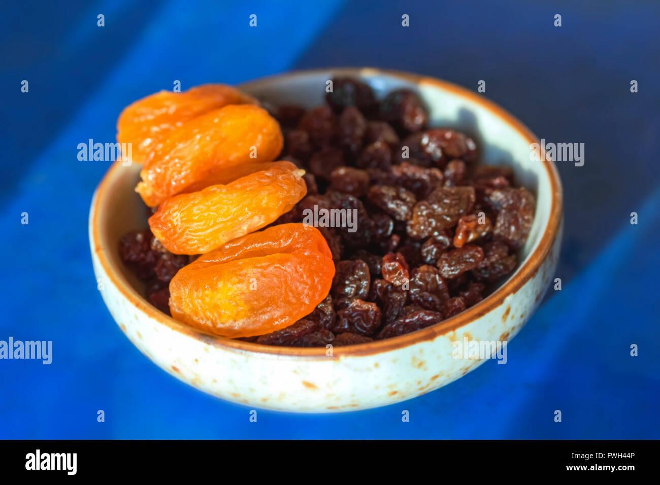 Abricots secs et raisins secs dans peu de plaque sur fond bleu Banque D'Images