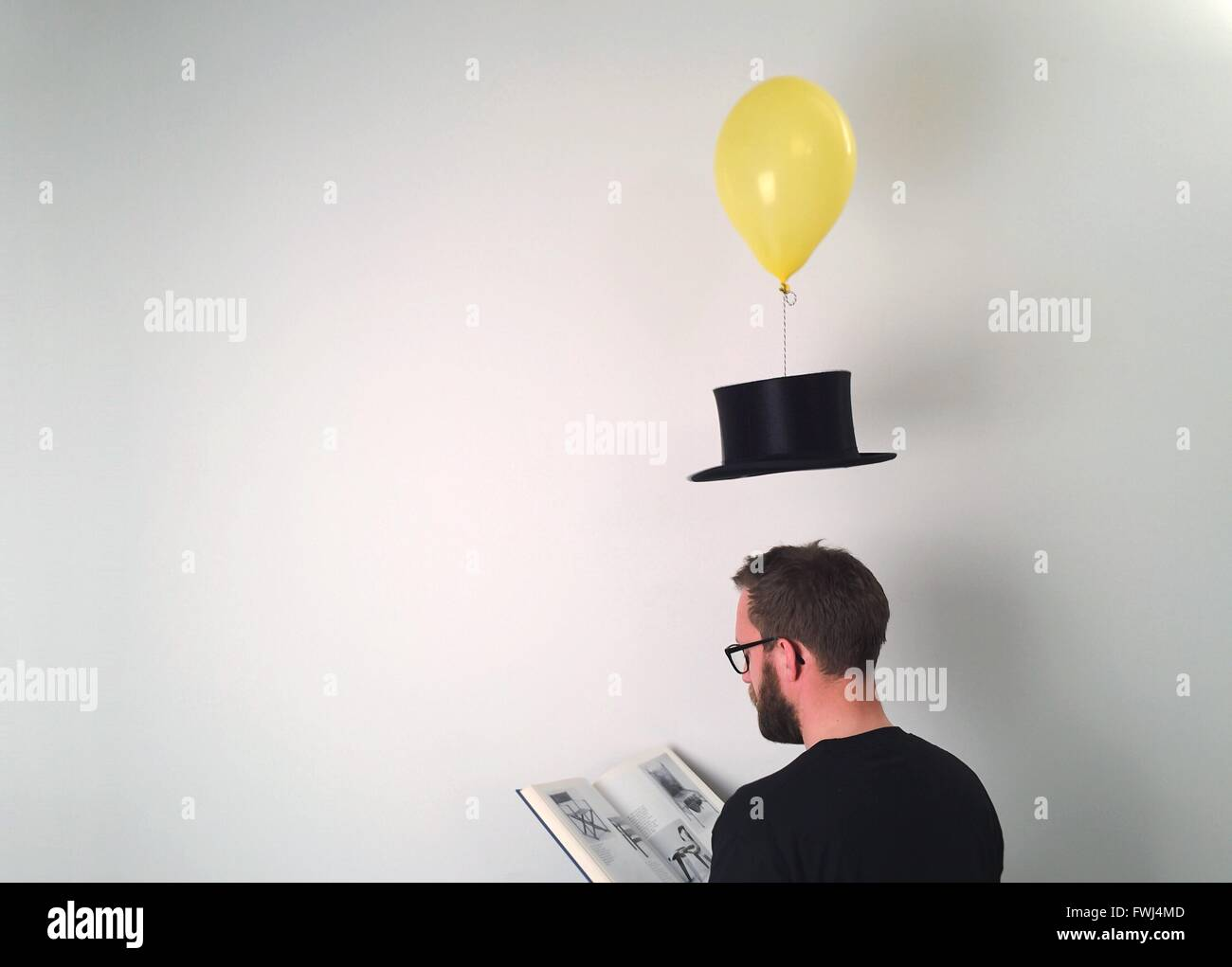 Man reading Book alors que Hat liée à Balloon Over White Background Photo Stock