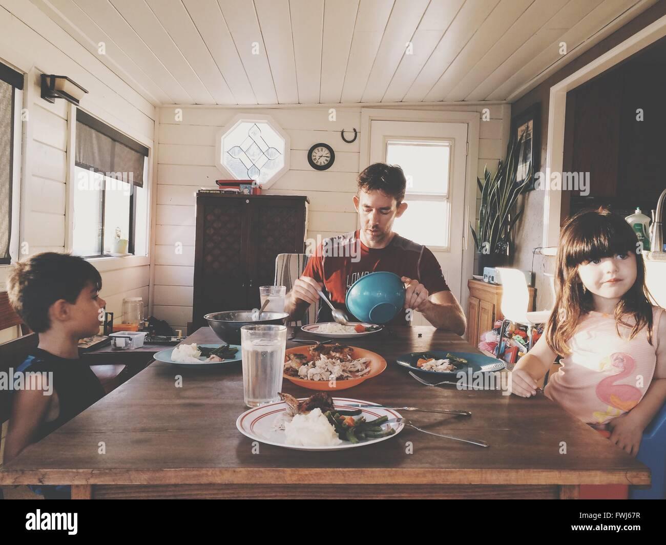 Père avec les enfants déjeunant à la maison Photo Stock