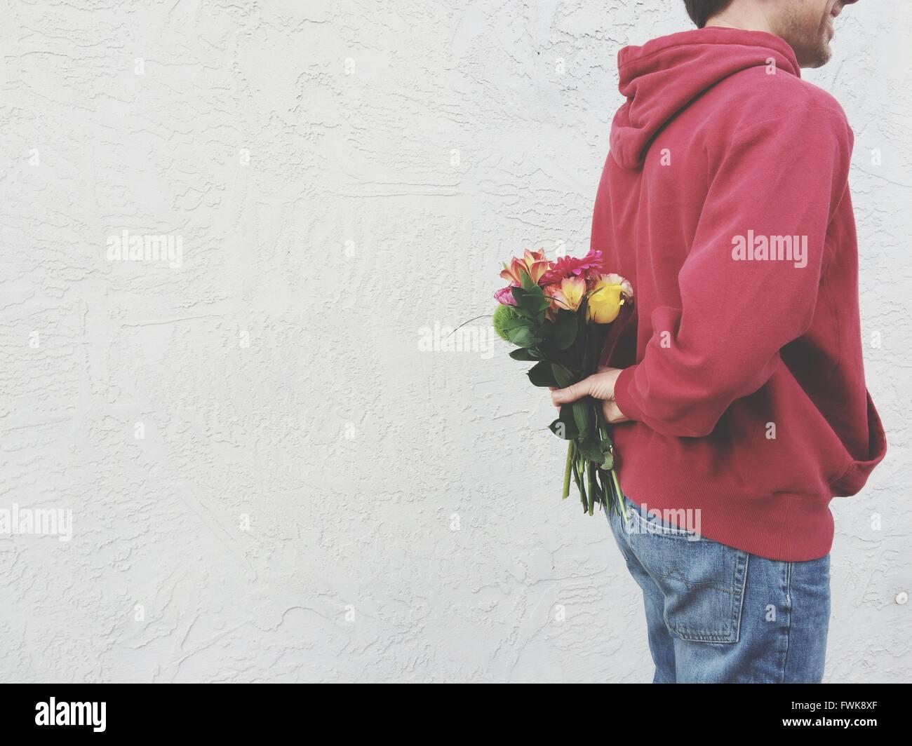 Portrait Man Hiding Bouquet dos contre mur Photo Stock