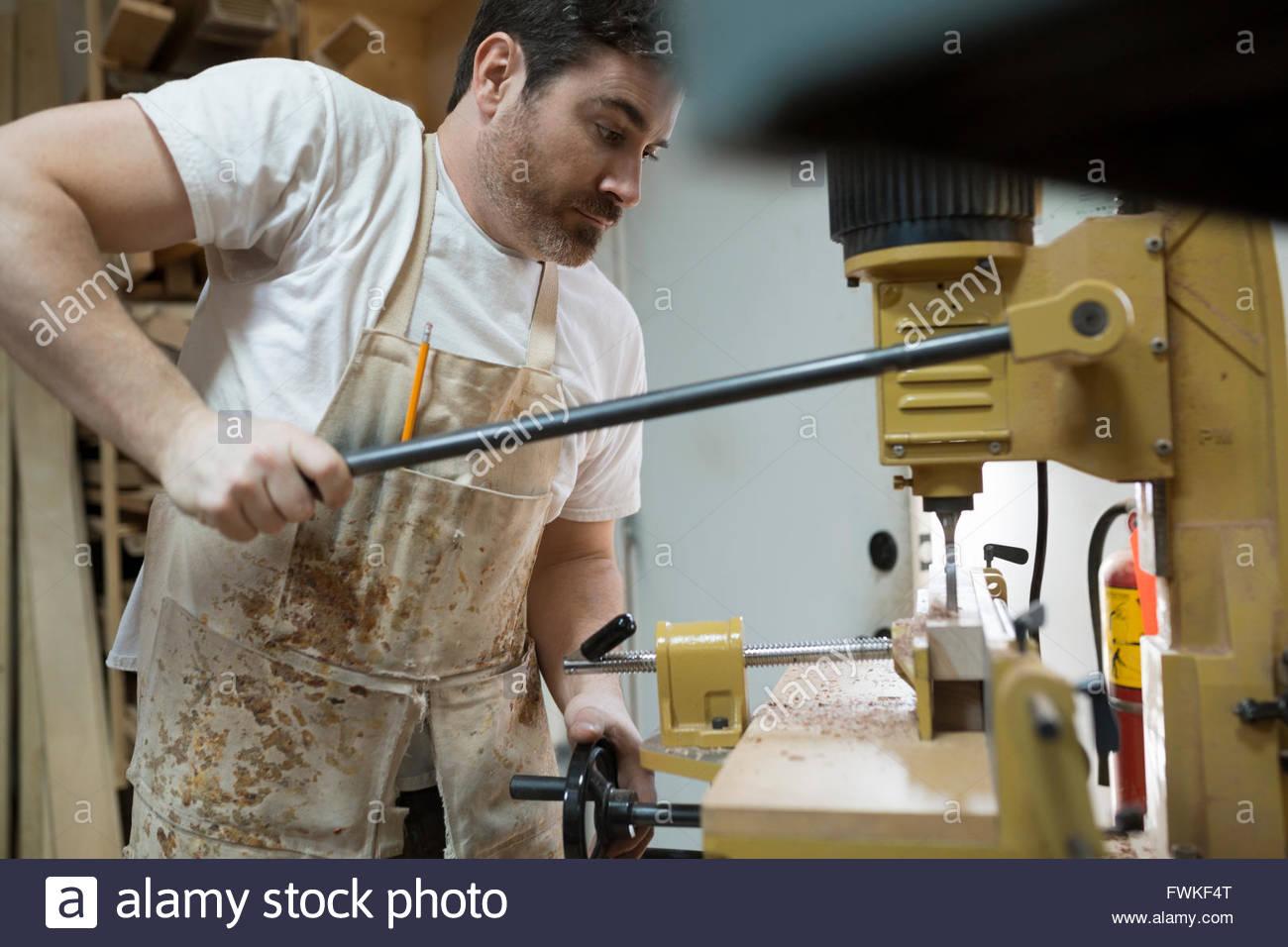 Carpenter en utilisant la perceuse en atelier Photo Stock