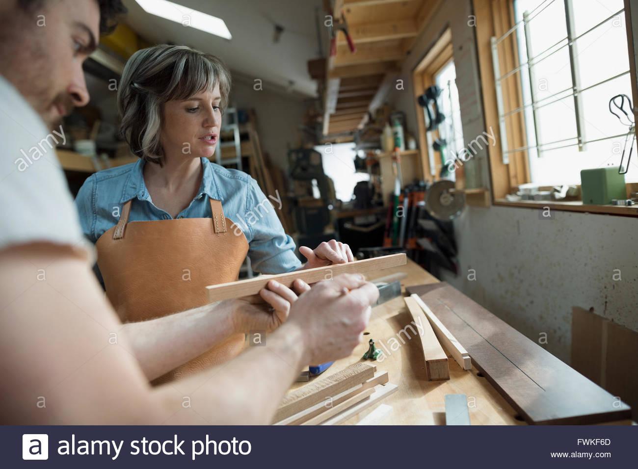 Les charpentiers l'examen de morceau de bois dans l'atelier Photo Stock
