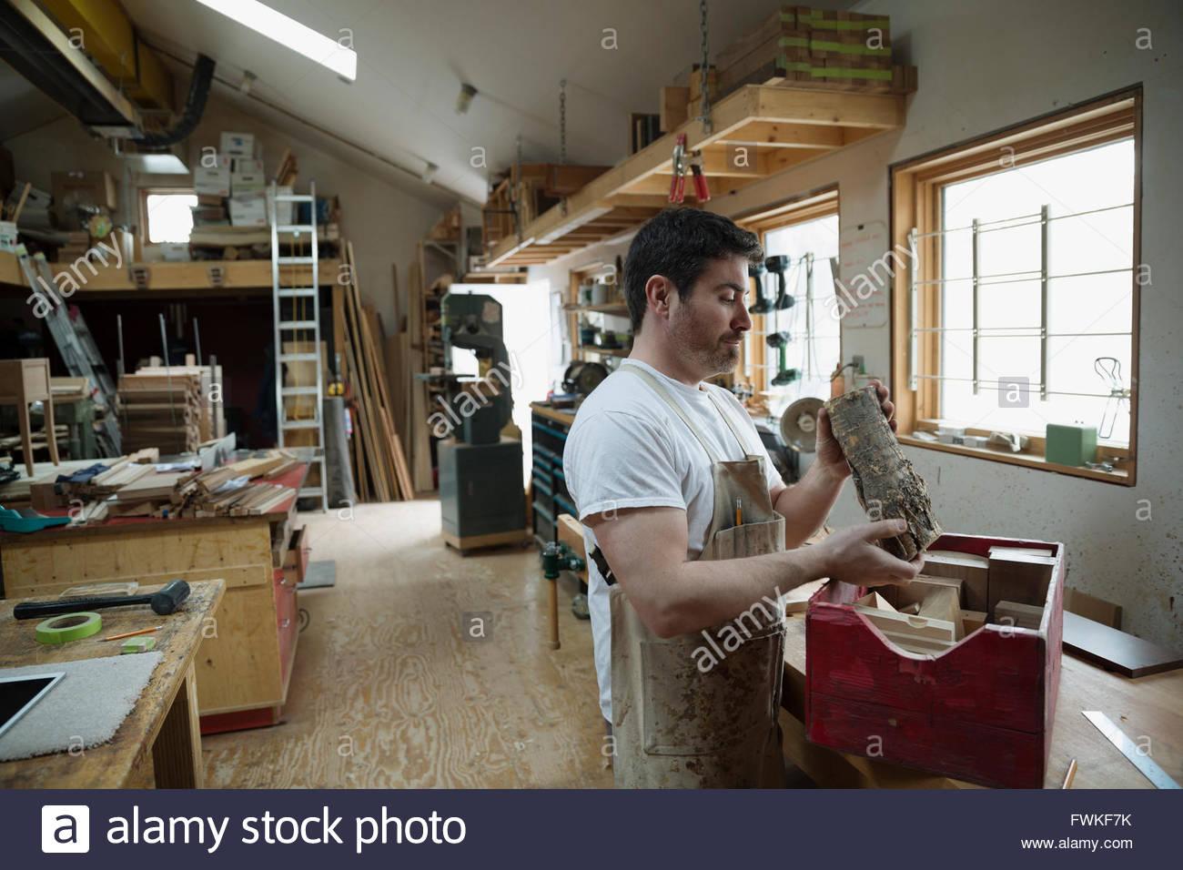 Carpenter l'examen de morceau de bois dans l'atelier Photo Stock