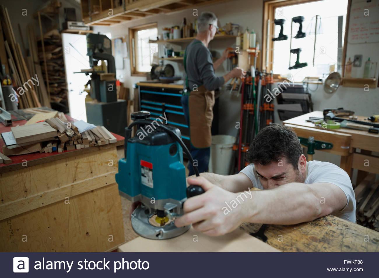 Carpenter à l'aide de mains vu en atelier Photo Stock