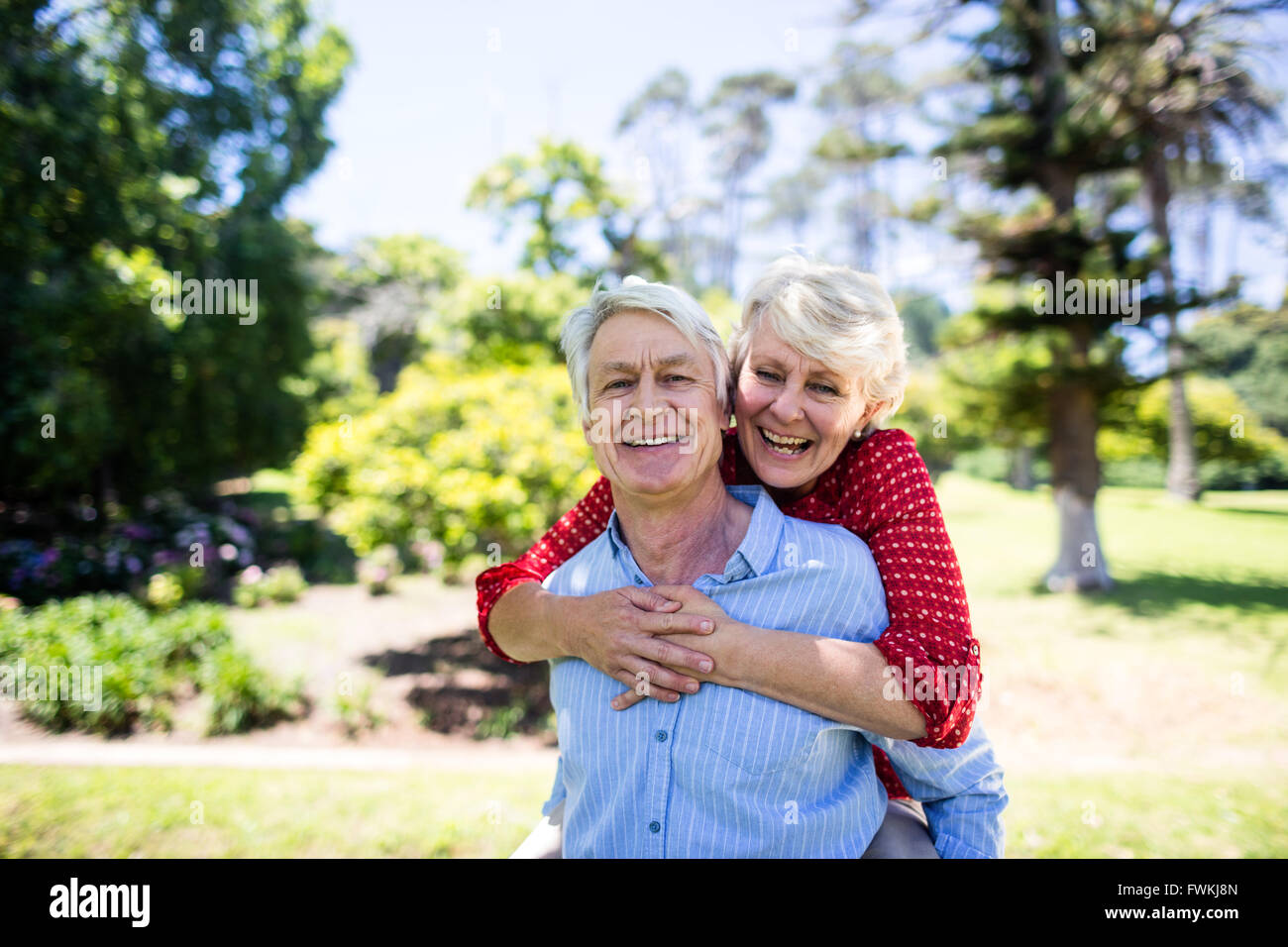 Happy senior man giving a piggy back to senior woman Photo Stock
