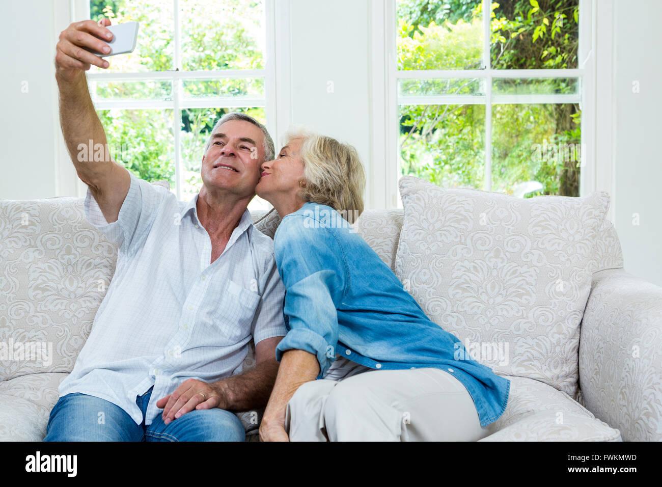 Senior woman kissing tandis que l'homme en tenant salon en selfies Banque D'Images