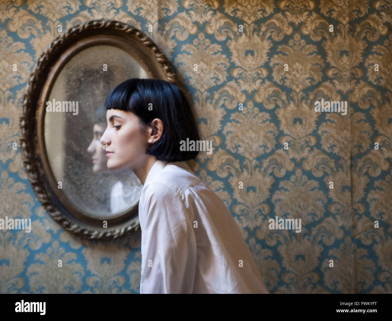 Vue latérale du miroir à la maison femme contre Photo Stock