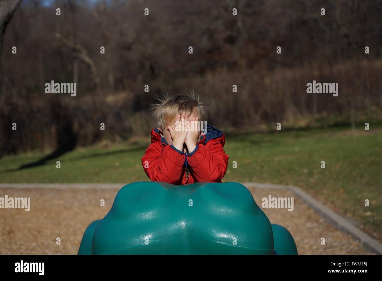 Boy Hiding Face à l'aire de jeux Photo Stock