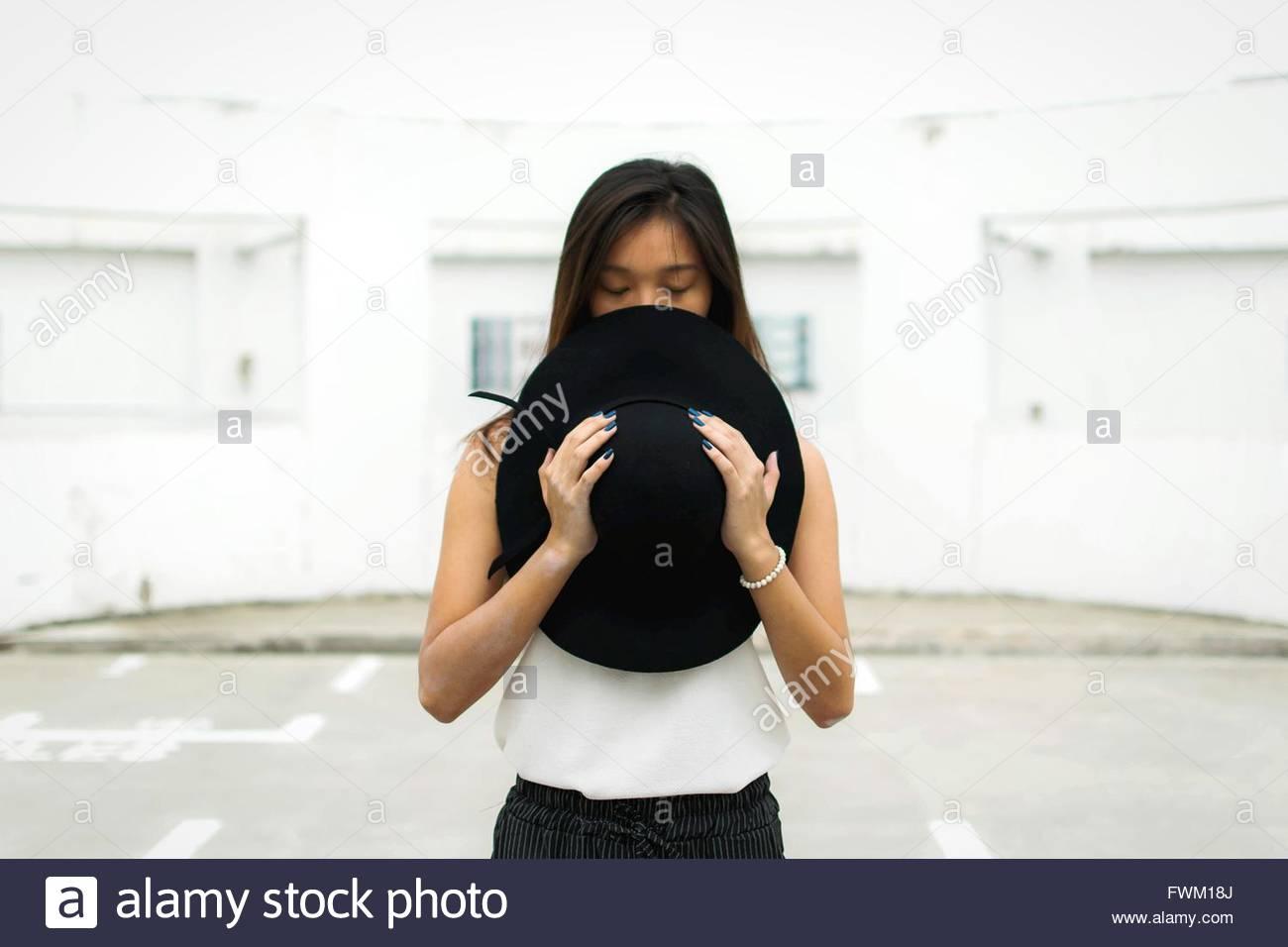 Woman Holding Hat le sentier contre le bâtiment Photo Stock