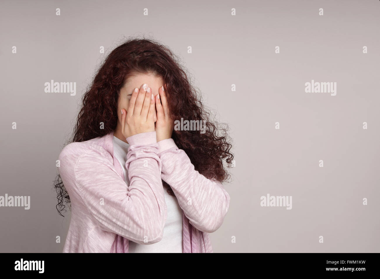 Jeune femme se cacher face debout contre le mur Photo Stock