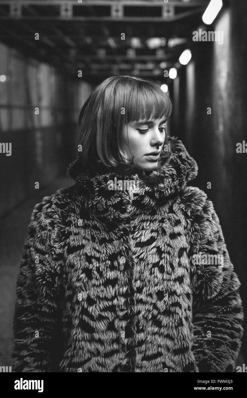 Belle Jeune femme portant manteau de fourrure debout dans le métro Photo Stock