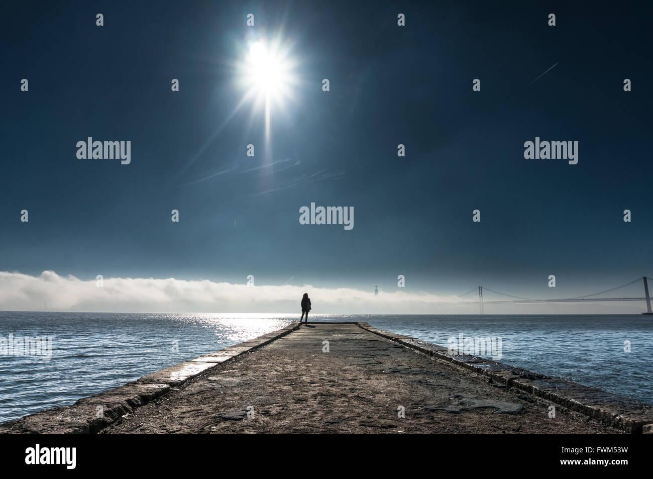 Distance de vue personne debout sur la jetée au-dessus de la mer contre le ciel Photo Stock