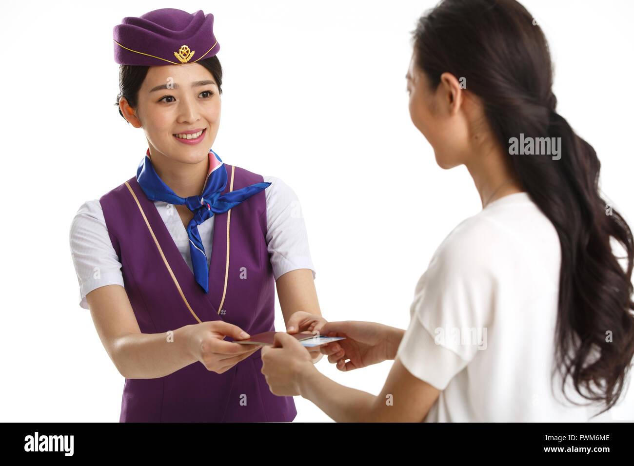 Les jeunes femmes de bord pour les clients de passer d'un passeport Photo Stock