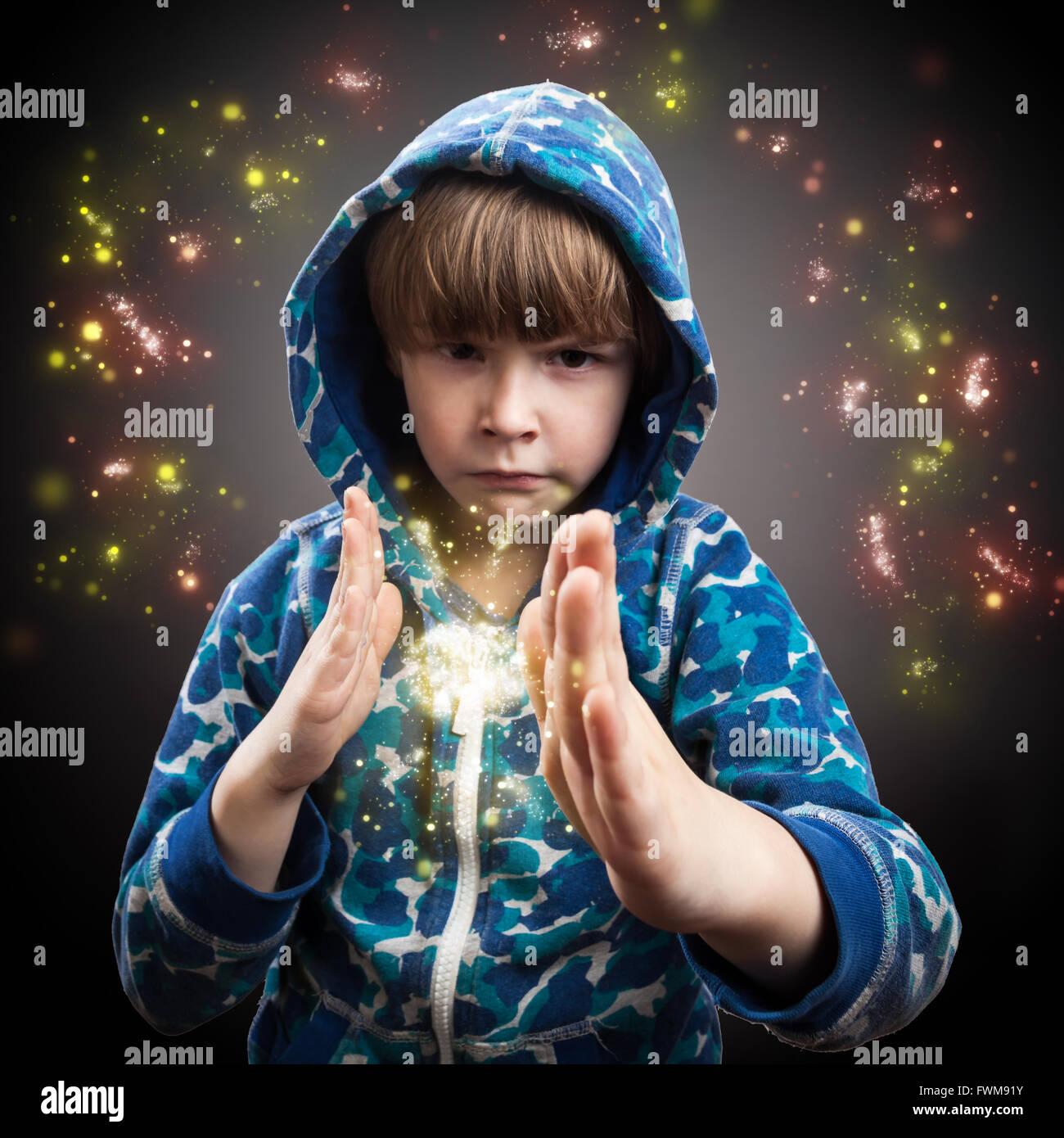 Portrait de garçon magicien avec Sparkles contre l'arrière-plan gris Photo Stock