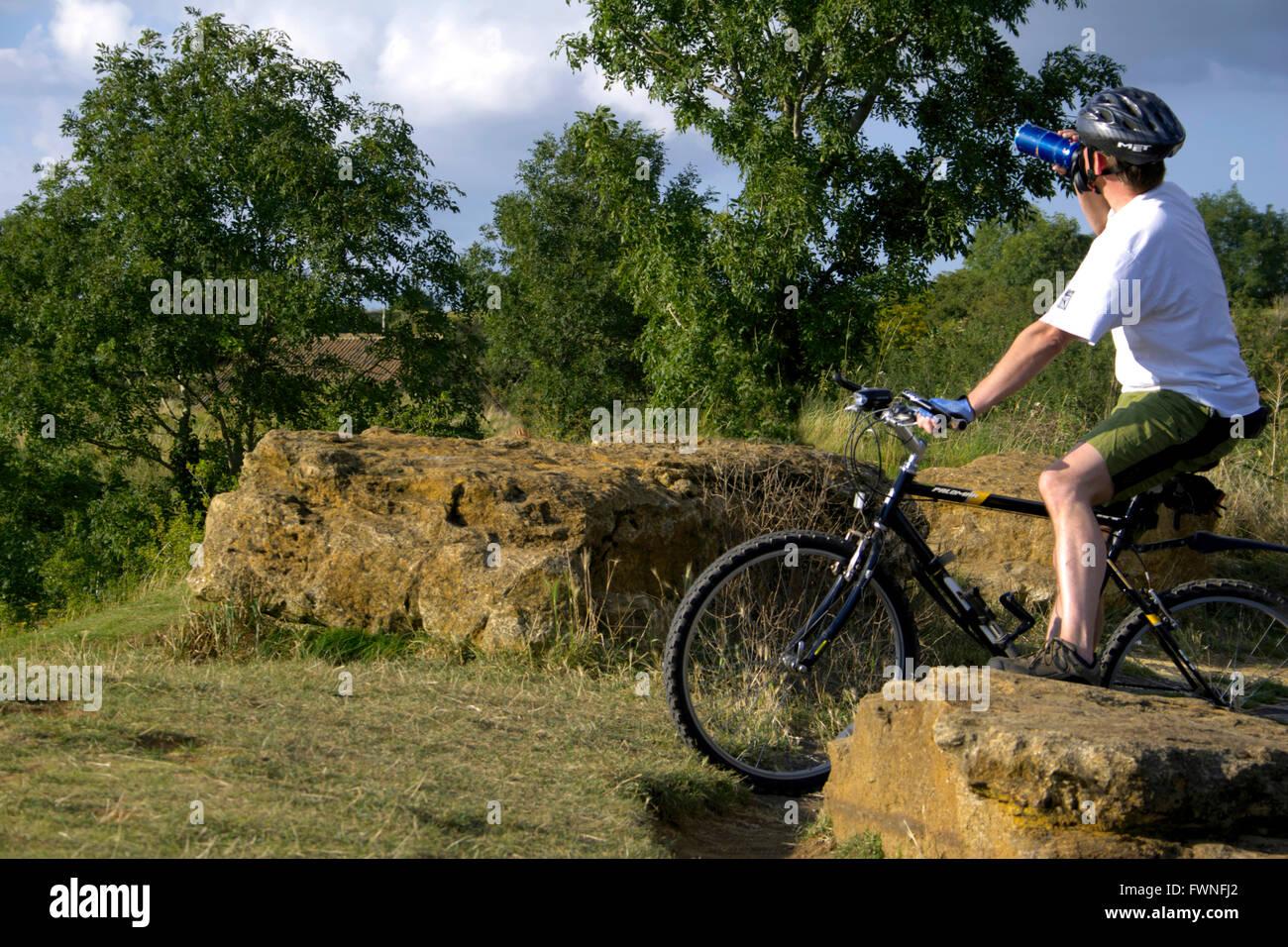 Cycliste sur Ham Hill, Somerset, Angleterre, les gens jeune homme reposant repose sur l'eau de boisson potable rock bouteille vélo assis Banque D'Images