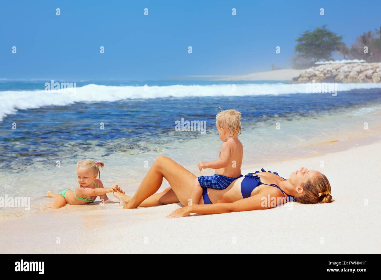 Happy Family - mère, fils et fille bébé couché sur la plage de sable et de regarder en mer surf Photo Stock