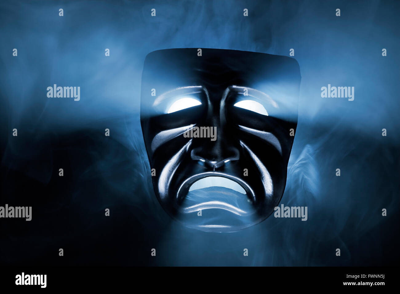 Masque noir avec lumière provenant de ses yeux et de la bouche. Photo Stock