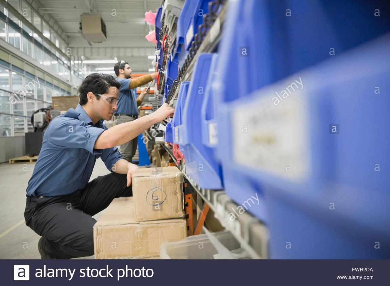 Cueillette de travailleur dans l'entrepôt de pièces Photo Stock