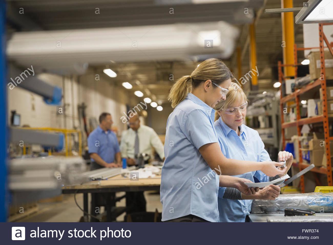 Les travailleuses de l'inspection de pièces dans l'usine de fabrication Photo Stock