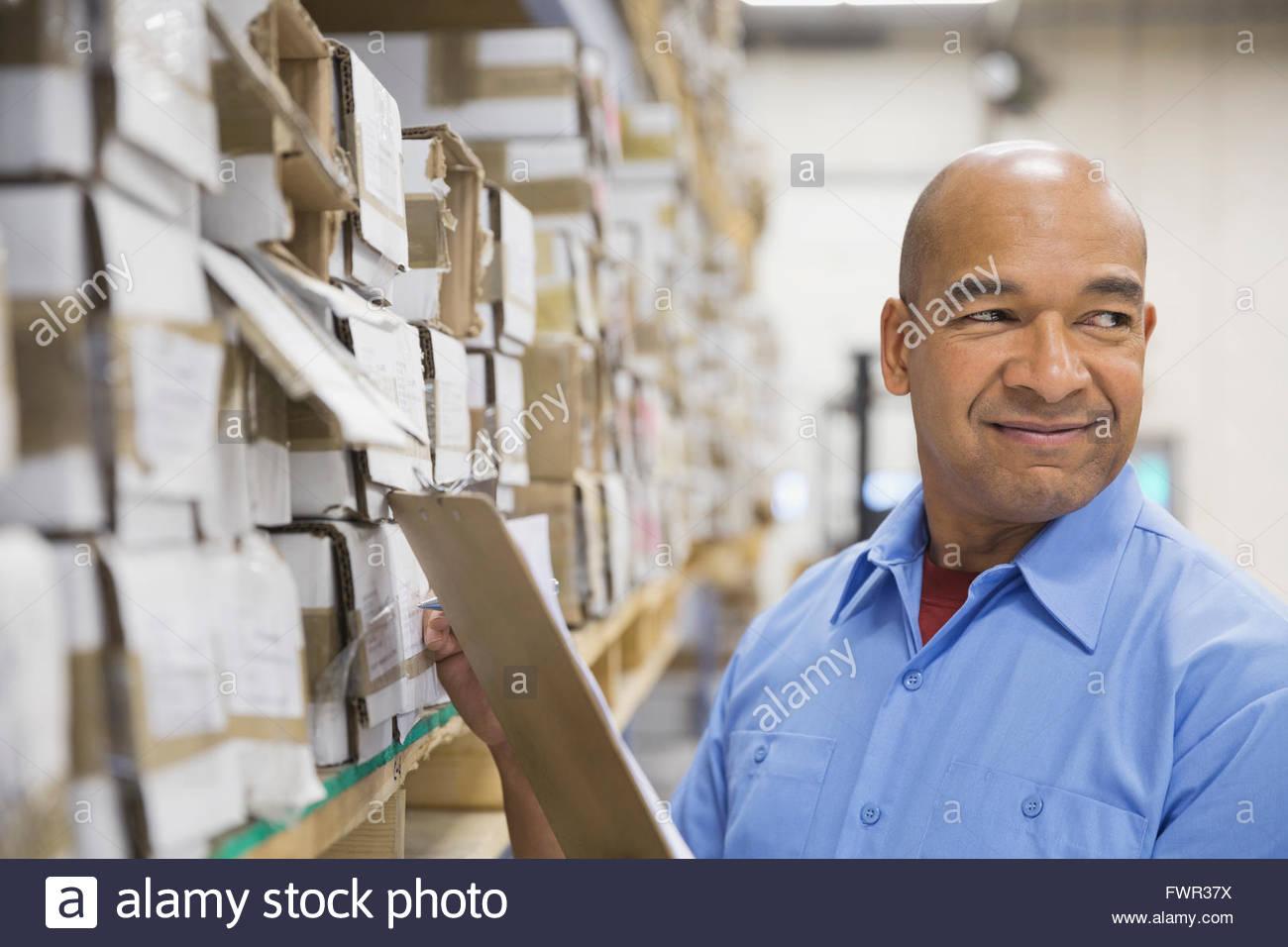 Travailleur masculin avec clipboard in warehouse Photo Stock