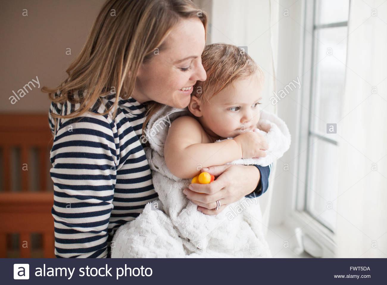 Mère se pelotonnant baby girl après son bain Photo Stock