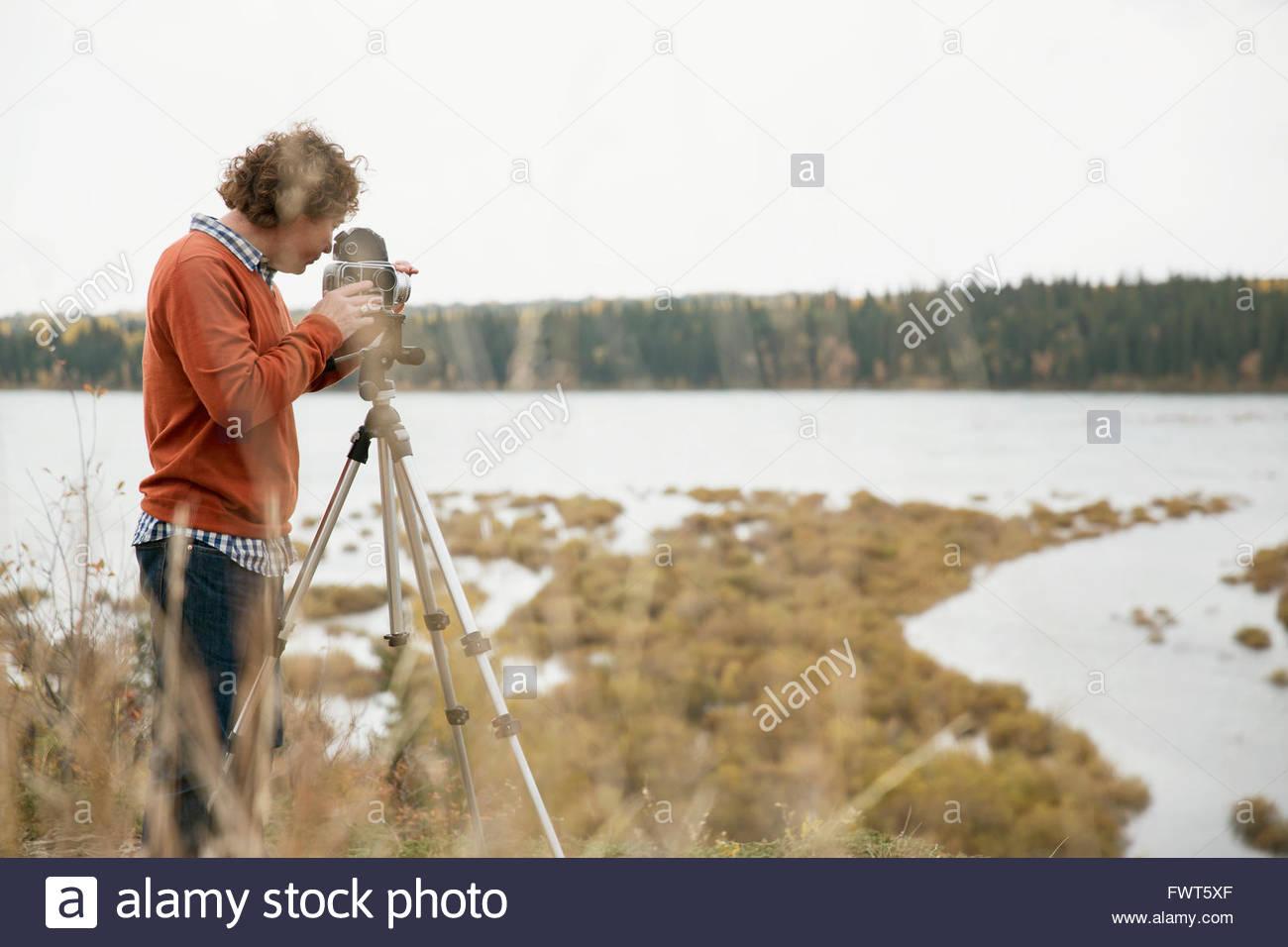 Homme mûr à l'aide d'appareil photo sur trépied Photo Stock