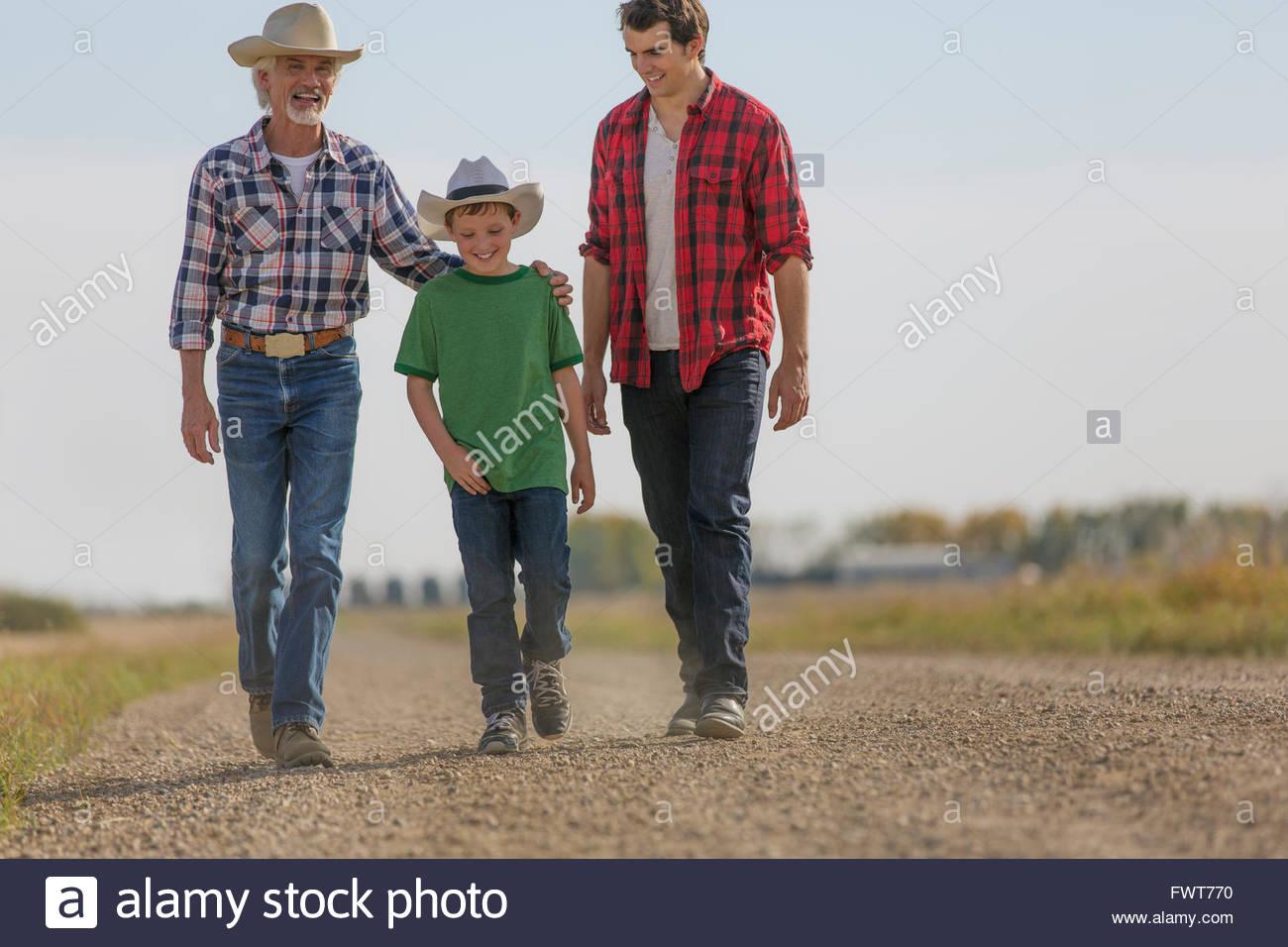 Trois générations d'hommes marchant sur la route rurale. Photo Stock