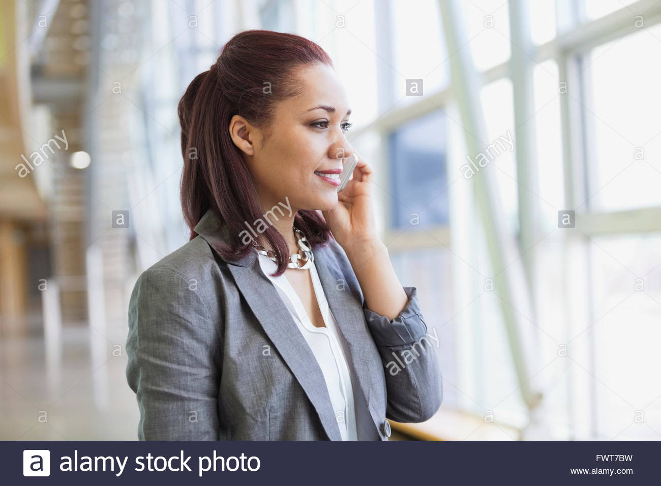Businesswoman using mobile phone by window in office Banque D'Images