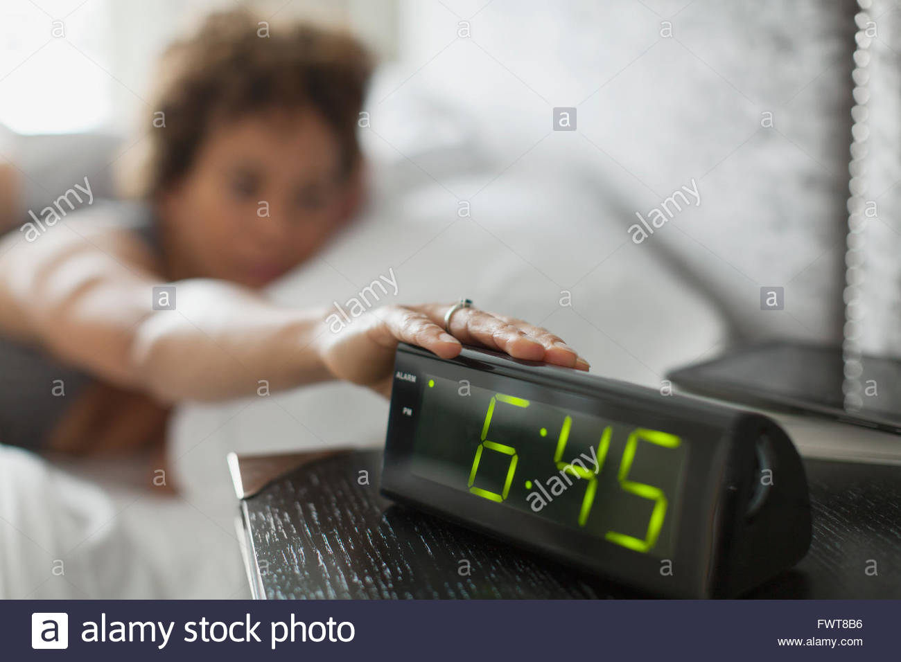 Woman Reaching for bouton snooze sur réveil. Photo Stock