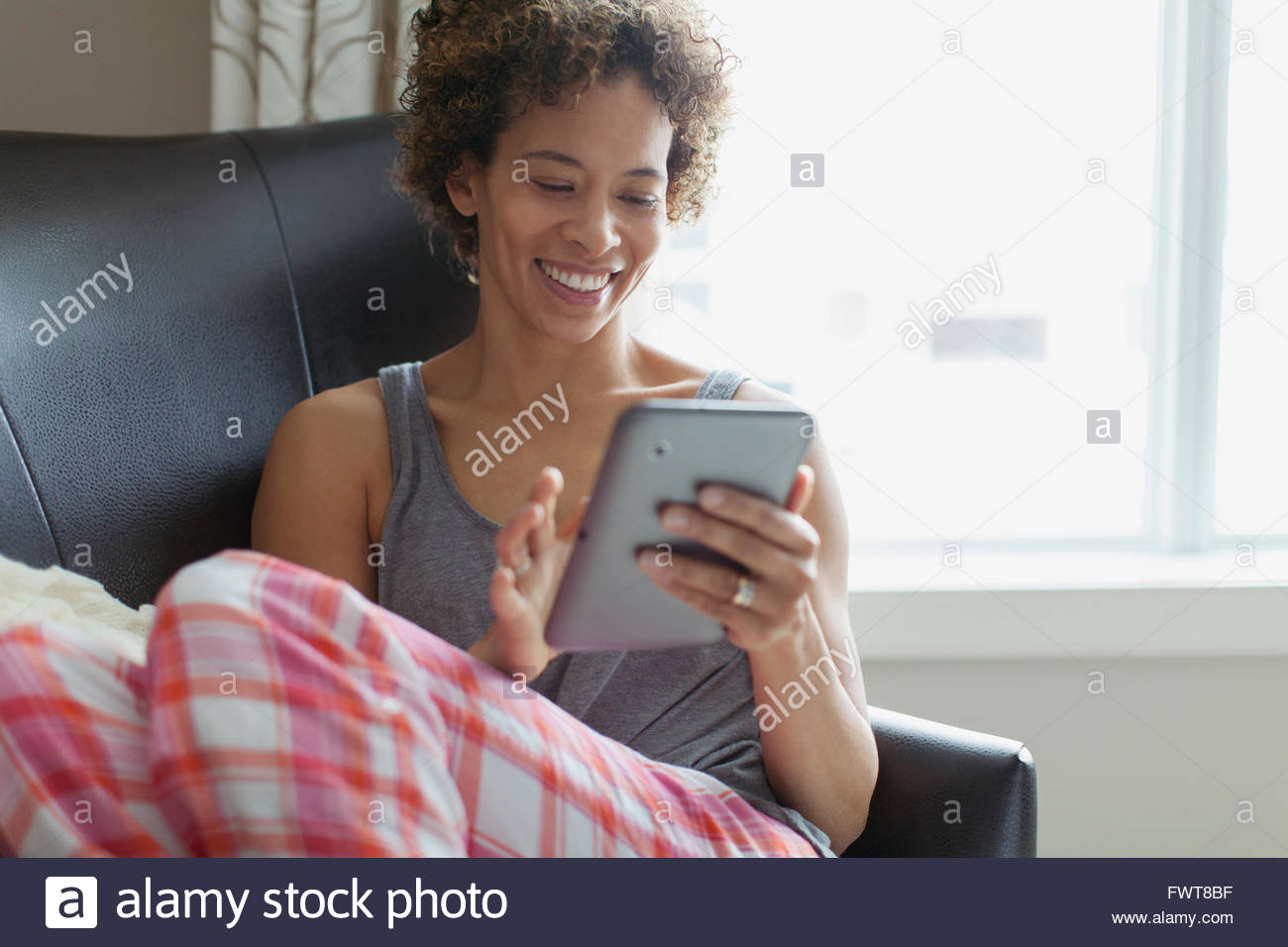 Woman using tablet computer at home. Photo Stock