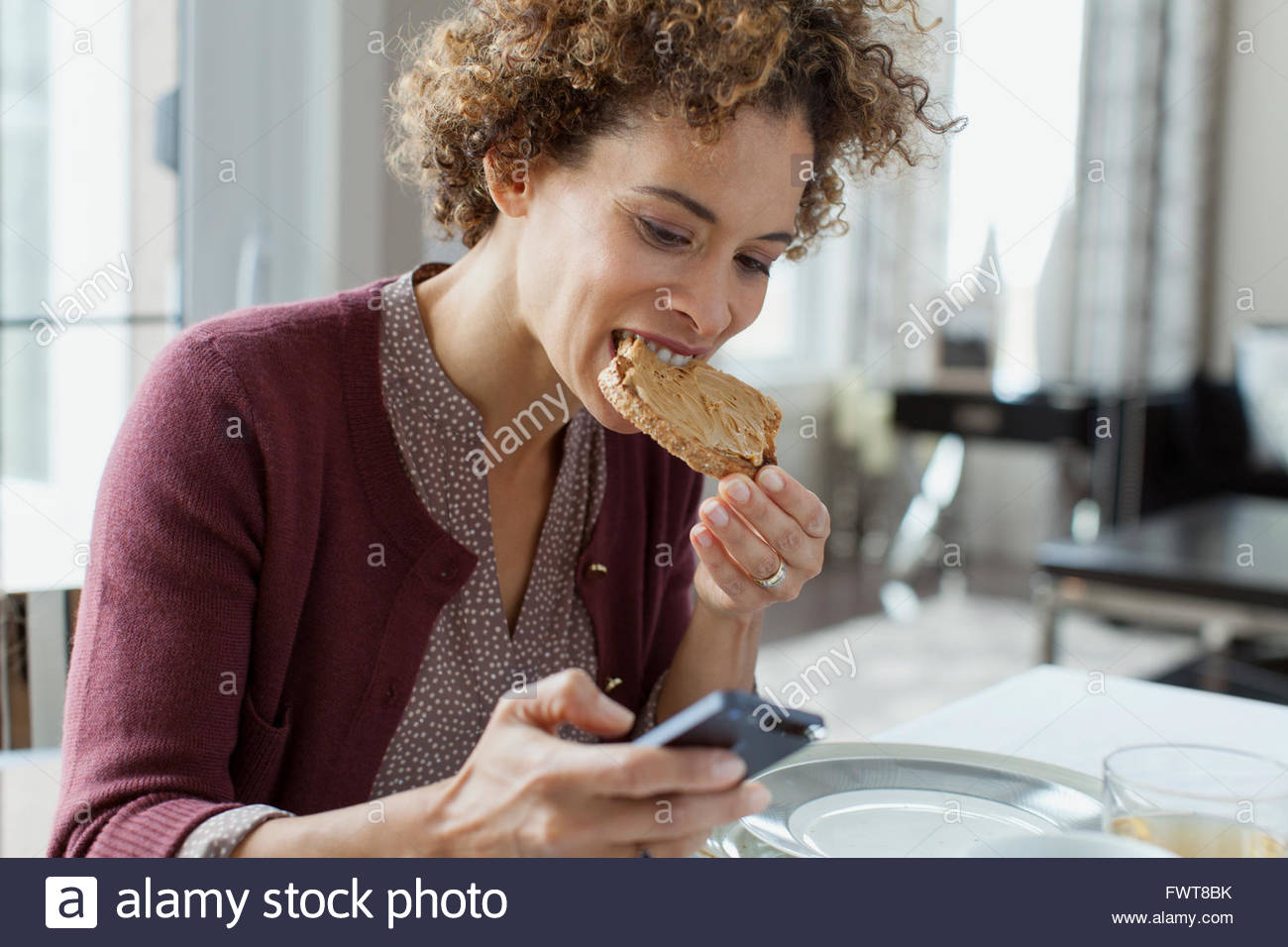 Woman eating toast lors de la vérification de smartphone. Photo Stock