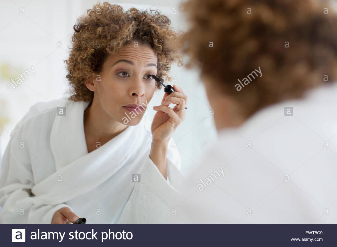 Woman applying make-up en miroir. Photo Stock