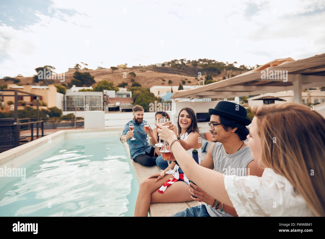 Tourné en extérieur de professionnels jeunes assis sur le bord de la piscine après avoir pousser un toast. Les amis Banque D'Images