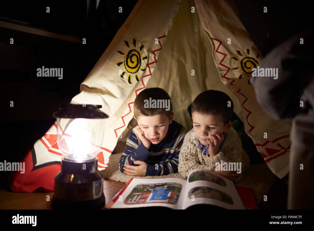 Deux jeunes garçons de la lecture à l'intérieur de tente installée à l'intérieur Photo Stock