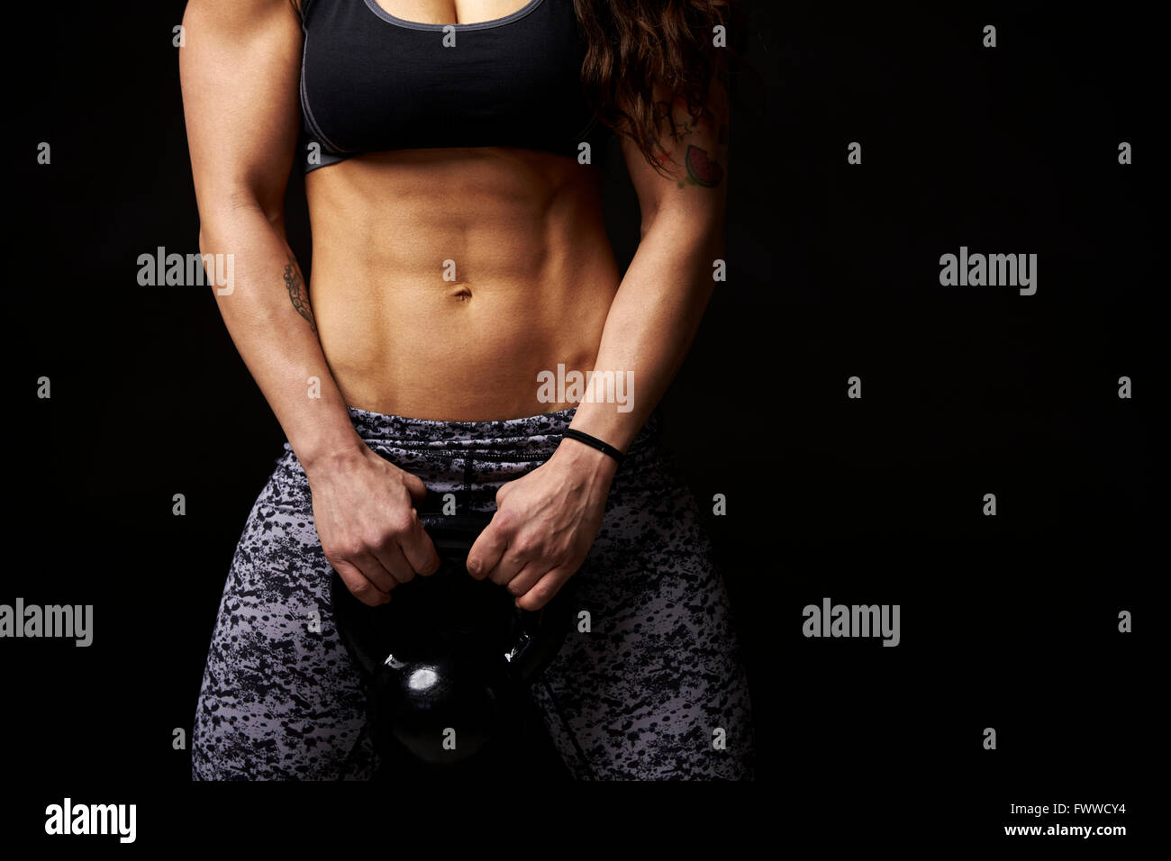 La mi-section de culture jeune femme musculaire kettlebell de levage Photo Stock