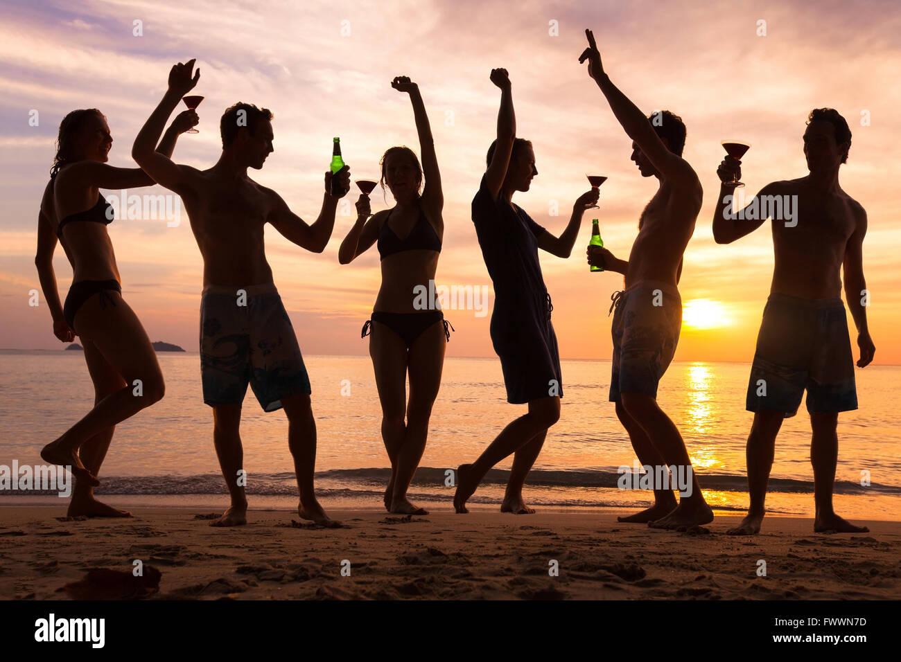 Beach Party, groupe de jeunes amis de la danse, boire de la bière et des cocktails au coucher du soleil Photo Stock