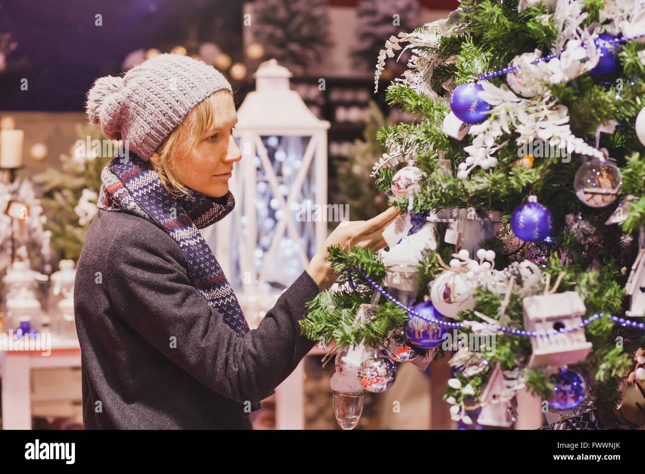 Nos gens au marché de Noël, le choix de la femme dans la boutique décoration de fête Photo Stock