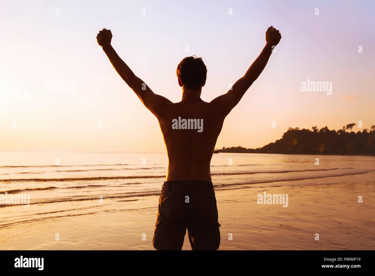 Contexte Le sport, silhouette de l'homme sportif solide sur la plage, gagnant ou concept de réalisation Photo Stock